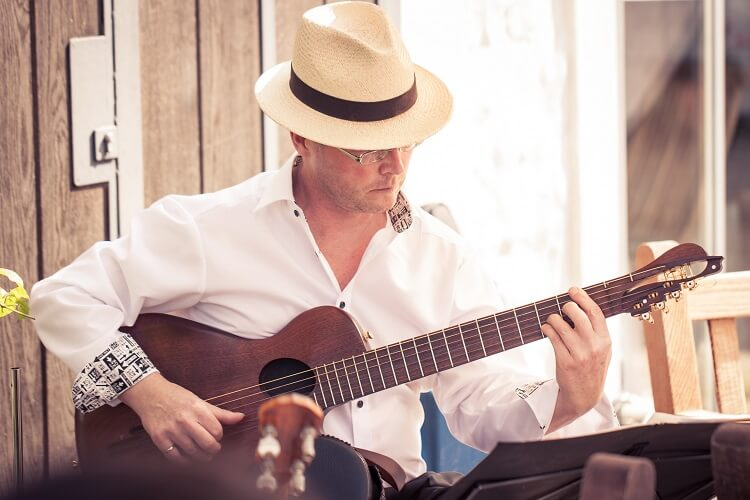 Livemusik auf der Gitarre als Hintergrundmusik beim nachmittäglichen Kaffeetrinken auf einer Hochzeitsfeier
