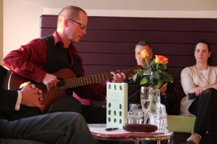 Während eine Talk-Runde spielt Martin Hoepfner musikalische Einlagen auf der Gitarre