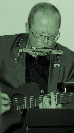 Martin Hoepfner spielt Gitarre und Mundharmonika